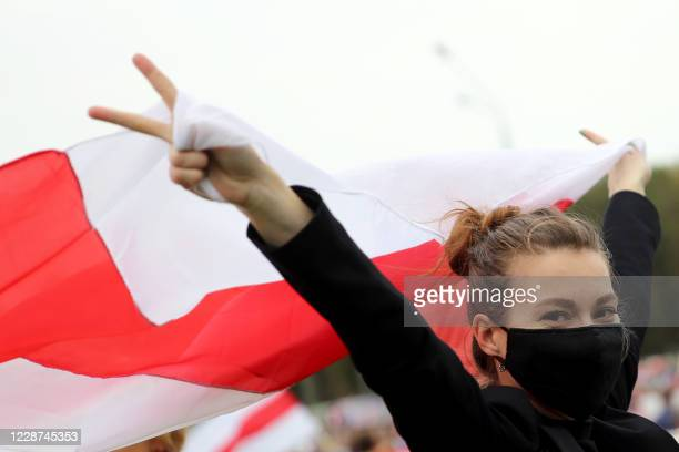An opposition supporter waves a former white-red-white flag of Belarus and flashes V-sign during an opposition rally to protest against the...