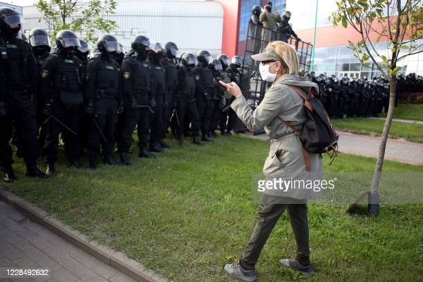 An opposition supporter wearing a face mask argues with law enforcement officers blocking the street during a rally to protest against the...