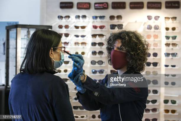 An optician right wearing a protective face mask and gloves checks the spectacles of a client on the first day of reopening in Athens Greece on...