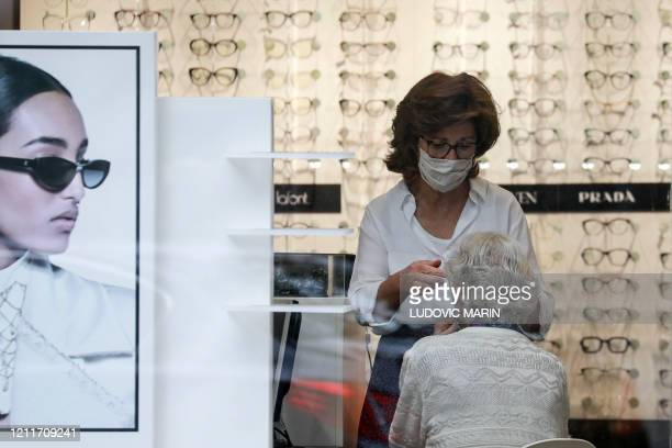 An optician wears a mask as she fits a new pair of spectacles to a client with an appointment at a shop in Paris on May 4 on the fortyninth day of a...