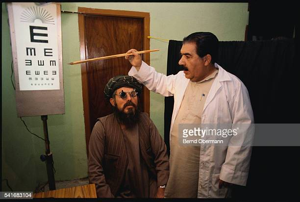 An optometrist examines an Afghan refugee at the United Medical Center of Afghan Mujahid Doctors in Peshawar Pakistan