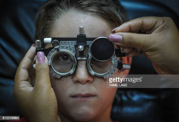 An optometrist makes a vision test to a child at a clinic in Havana on July 6 2017 / AFP PHOTO / Yamil LAGE