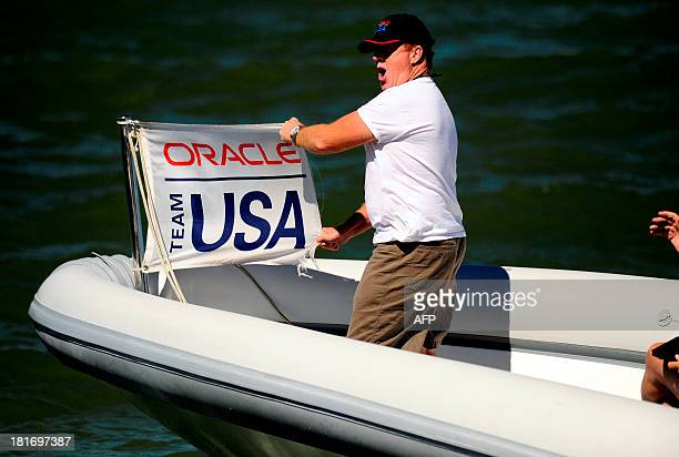 An Oracle Team USA fan expresses jubilation as he passes spectators from a boat during race 16 of the 34th America's Cup on September 23 2013 in San...