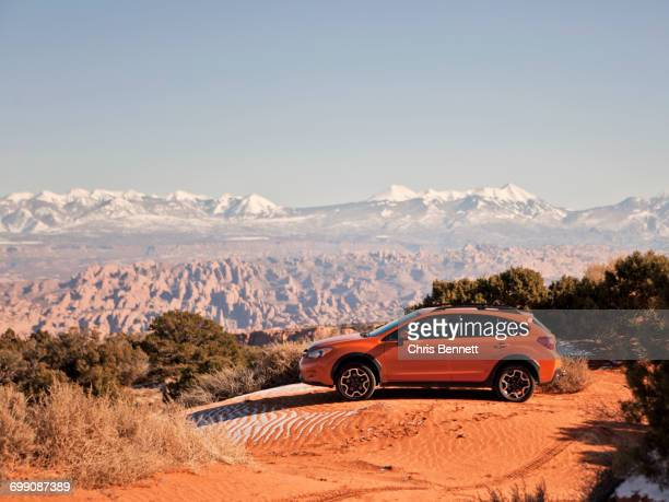 an orange car sits parked on a sand dune with the desert stretching out behind. - 固定された ストックフォトと画像