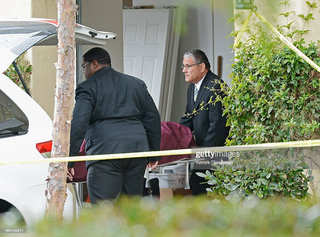 An Orange County Coroner picks a body of a victim from a house on February 19, 2013 in Ladera Ranch, California. According to law enforcement officials six people were shot in cities of Tustin, Ladera Ranch and Orange, four of them fatally, including the suspected shooter, who apparently killed himself.