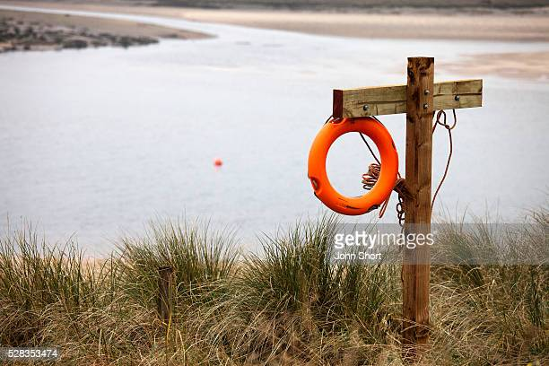 An orange life preserver hangs on a wooden structure at the water's edge; alnmouth northumberland england