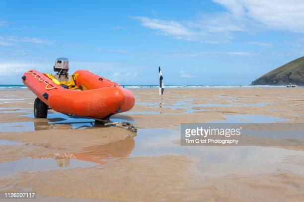 an orange rigid inflatable boat (rib) on a beach - cornish flag stock pictures, royalty-free photos & images