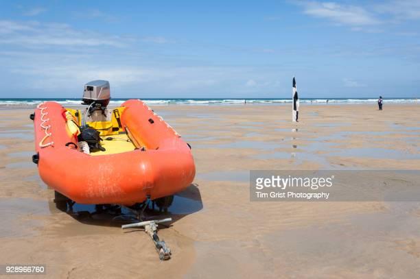 An Orange Rigid Inflatable Boat (RIB) on a Beach