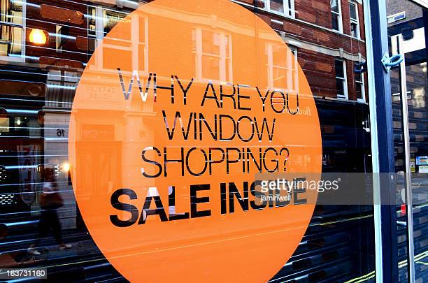 An orange sale sign on a store window