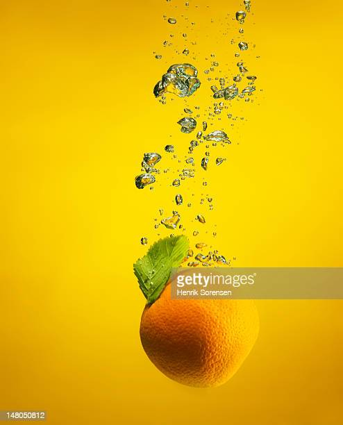 An orange splashed into water