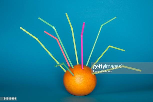 An orange with a bunch of drinking straws stuck into it