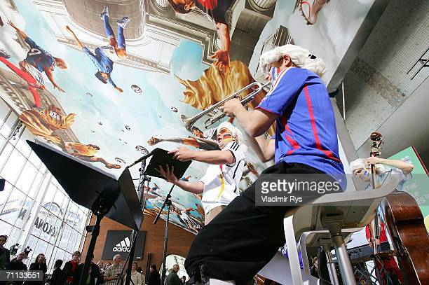 An orchestra plays music during the presentation of a huge 800 square meter World Cup Themed adidas poster at the entrance hall of the Cologne...