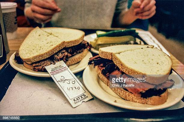 An order ticket lies amongst pastrami on rye and brisket on rye sandwiches with a plate of pickles at Katz's Delicatessen in Manhattan New York USA...