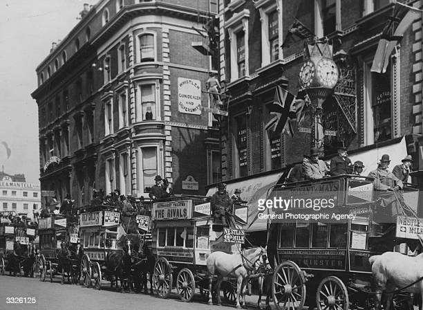 An orderly line of horsedrawn buses at a stop in Charing Cross The open topped vehicles are covered with adverts