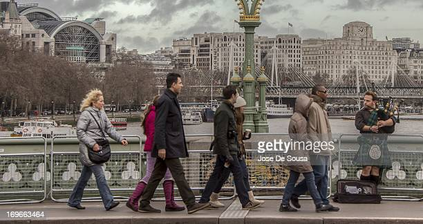 CONTENT] An orderly succession of people while a bagpiper plays on Westminster Bridge