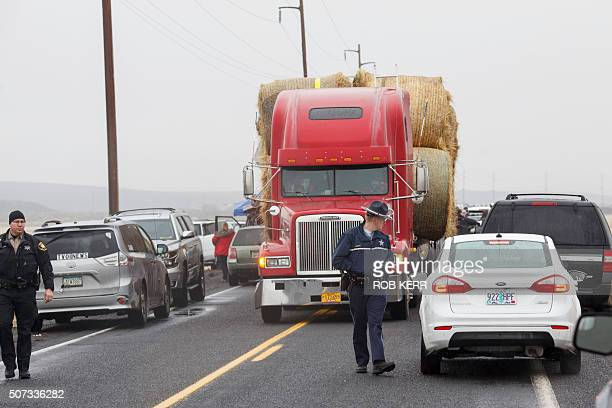 An Oregon State Police officer and a Washington County Sheriff deputy help guide a truck and trailer hauling hay through a narrow gap of media...