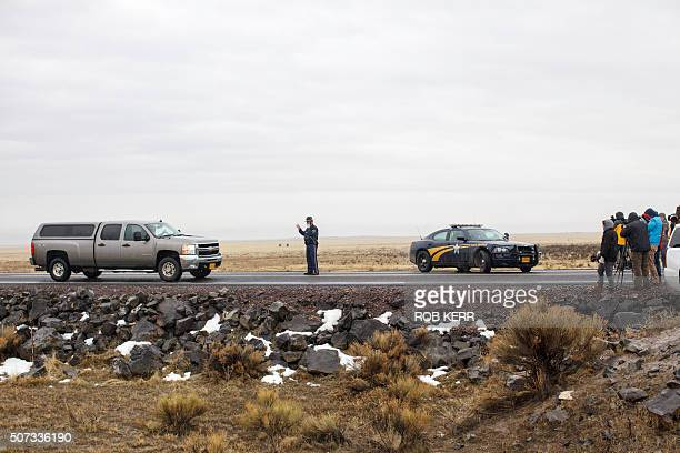 An Oregon State Police officer motions to a vehicle departing a closed area at a road checkpoint on Highway 78 approximately 4 miles from the Malheur...