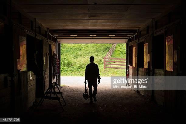 An organic farm in the Catskills. A man walking through a stable.