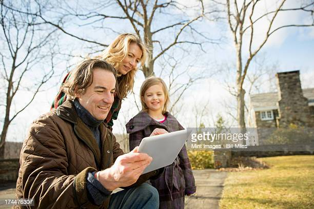 An Organic Farm in Winter in Cold Spring, New York State.  A man holding a digital tablet in his hands. A woman and a child.