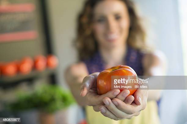 An organic fruit and vegetable farm. A woman holding a tomato.