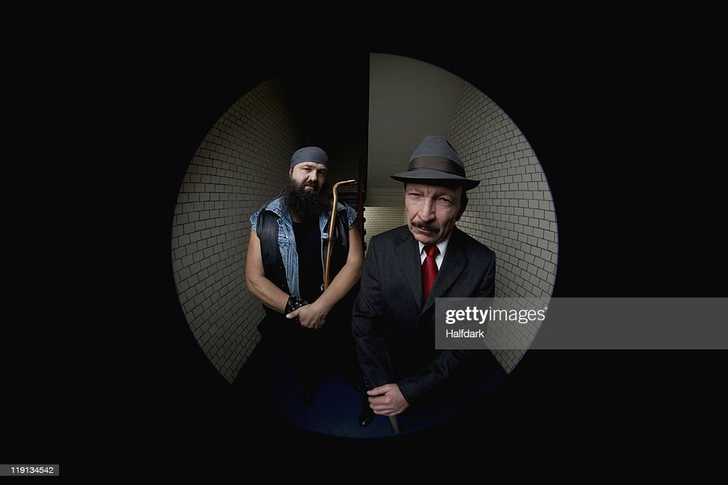 An organized crime boss with his bodyguard, viewed through a peephole : Stock Photo