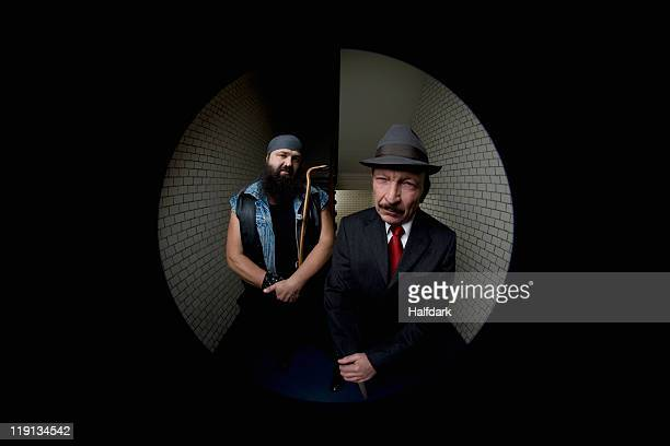 An organized crime boss with his bodyguard, viewed through a peephole