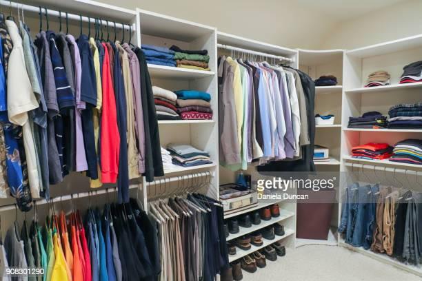 an organized man's closet - walk in closet stock photos and pictures