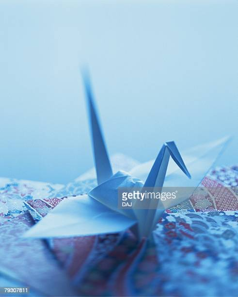 An origami crane on Japanese patterned papers, Close Up, High Angle View, Toned Image