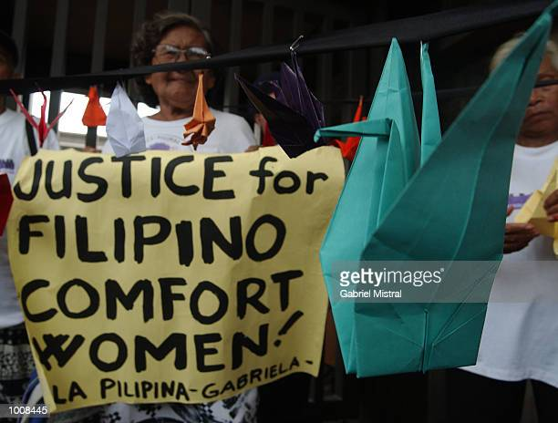 An origami dove sits next to a banner claiming justice for Filipino comfort women during a protest to express the plight of women who were used as...
