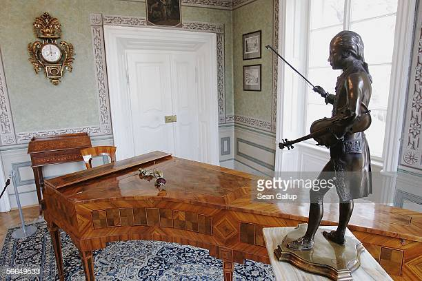 An original harpsichord used by Austrian composer Wolfgang Amadeus Mozart stands next to a statue of him in the room where Mozart stayed and composed...