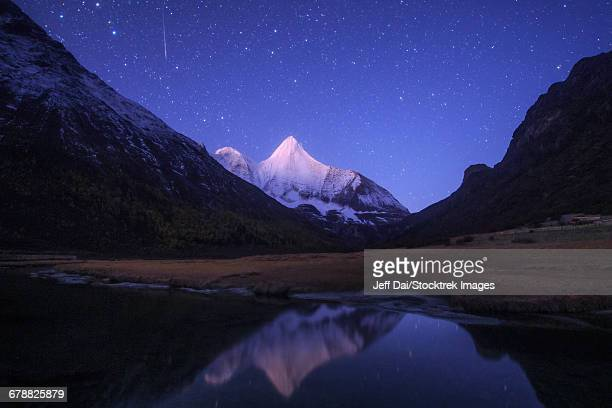 An Orionid meteor steaks over the Jampayang snow mountain in China.