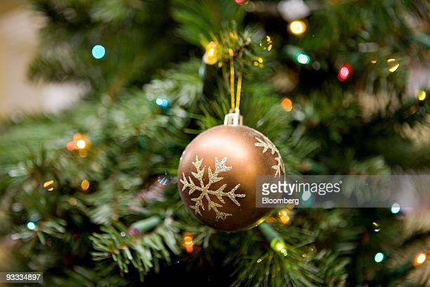 an ornament hangs from an artificial christmas tree on display inside a home depot store in