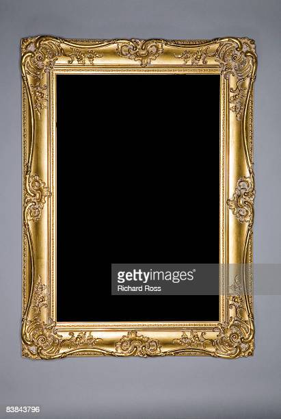 an ornate gold frame on a grey-blue wall - embellishment stock pictures, royalty-free photos & images