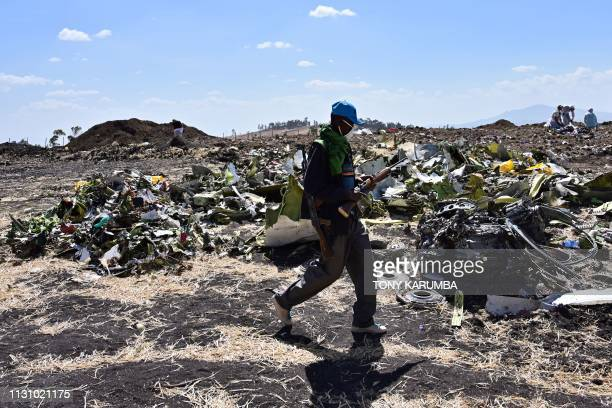 An Oromo man hired to assist forensic investigators walks by a pile of twisted airplane debris at the crash site of an Ethiopian airways operated...
