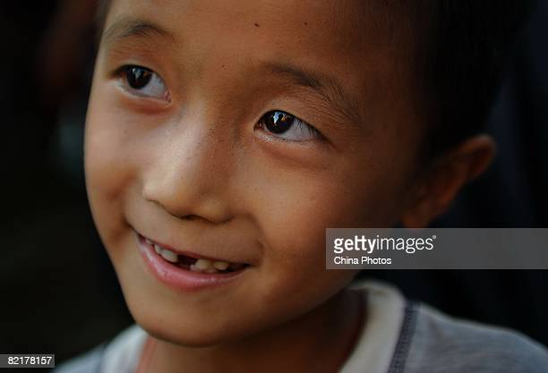 An orphan reacts to Chinese journalist Chen Xuebin who came to visit him at the Jiuxian Village on June 21 2008 in Zhanjiang of Guangdong Province...