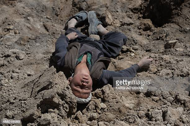 An orphaned young Afghan villager, who lost his family in the landslide, lies in the dirt as he grieves at the scene in Aab Bareek village in Argo...