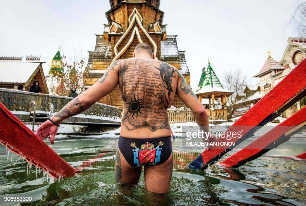 TOPSHOT An Orthodox believer enters the icy waters of a pond during the celebration of the Epiphany holiday in Izmailovo in Moscow on January 19 2018...
