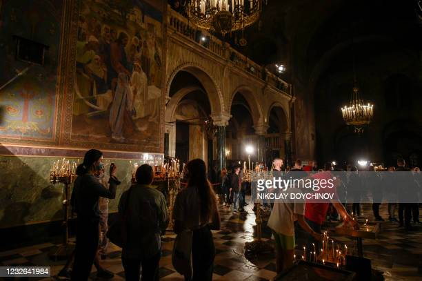 An Orthodox Christian believers light candles during an Easter midnight mass in the golden-domed Alexander Nevski Cathedral in Sofia on May 2, 2021.