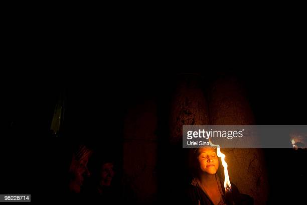 An Orthodox Christian is illuminated by burning candles during the Holy Fire ceremony in the Church of the Holy Sepulchre on April 3 2010 in...