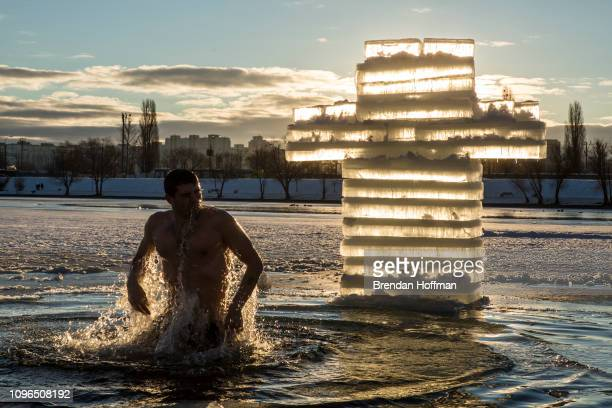 An Orthodox Christian man bathes in Telbin Lake near the Church of the Nativity of Christ for Epiphany on January 19 2019 in Kiev Ukraine The holiday...