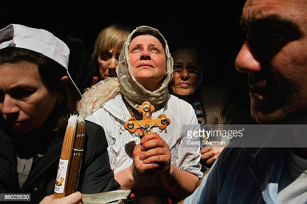 An Orthodox Christian pilgrim cries and prays as a ray of light highlights her during the Holy Fire ceremony in the Church of the Holy Sepulchre on...