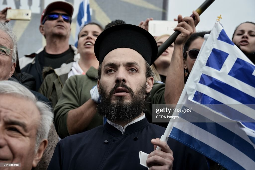 An Orthodox Christian priest holds the Greek national flag at the protest of 'Macedonia is Greek' against the use of name Macedonia by FYROM. Tens of thousands of protesters took to the street of Athens during the 'Macedonia is Greek' demonstration to protest their northern neighbor country (FYROM) use the term Macedonia to name their country.