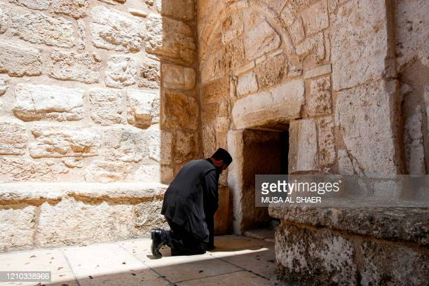 TOPSHOT An Orthodox Christian priest prays at the entrance of the Church of the Nativity in the biblical West Bank city of Bethlehem on April 18...