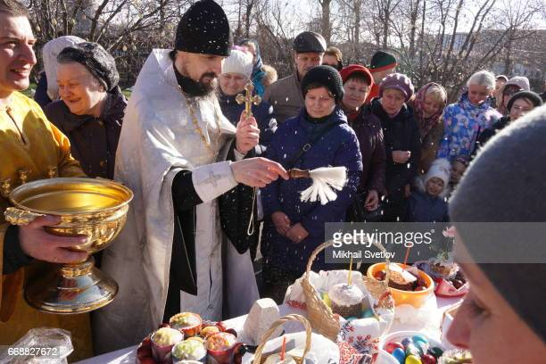 An Orthodox Church priest blesses the traditional Easter cakes and painted hard boiled eggs in preparation for Easter celebration at the LifeGiving...