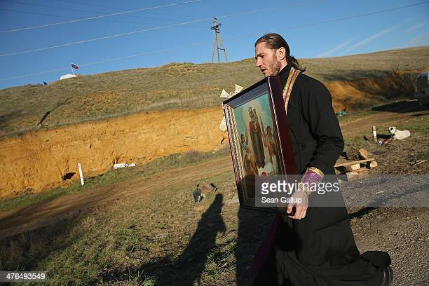 An Orthodox clergy member passes a hill where pro-Russian militants have dug foxholes and set up a sandbag position as he carries a religious icon...
