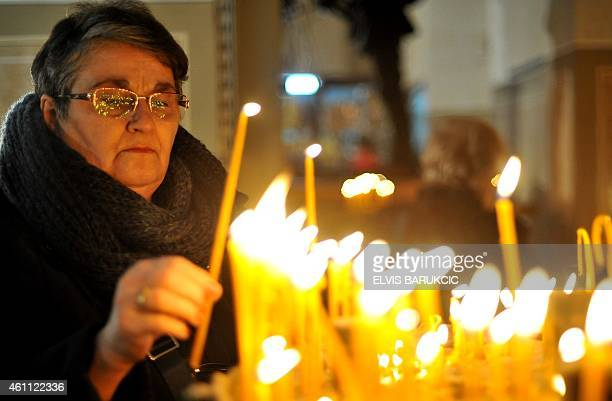An orthodox faithful lights a church candle on the Christmas morning service at the Congregational church in Sarajevo on January 7 2015 Bosnian...