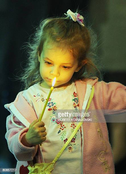 An Orthodox girl hold candles at the Sveti Kliment Ohridski Cathedral in Skopje during the Good Friday processions on April 252008 The Orthodox...