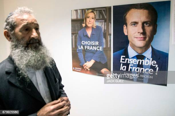 An Orthodox Jewish French citizen residing in Israel walks past election posters of independent centrist French presidential candidate Emmanuel...