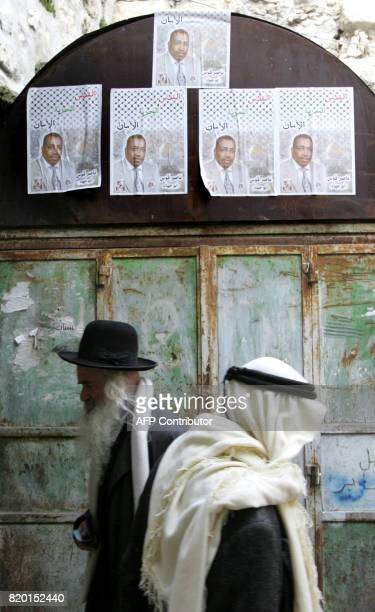 An Orthodox Jewish man and a Palestinian cross paths along a narrow street in the Old City of East Jerusalem 24 January 2006 a day prior to the...