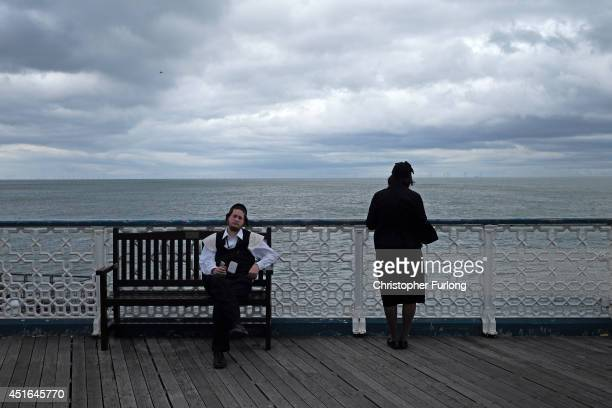 An Orthodox Jewish man relaxes on a bench as his wife prays looking out to sea from Llandudno pier on July 3 2014 in Llandudno Wales Llandudno is...